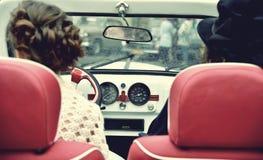 两中世纪礼服的卷曲女孩在葡萄酒汽车 例证百合红色样式葡萄酒 免版税库存照片