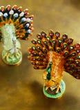 两中国人在金黄背景的孔雀小雕象 图库摄影