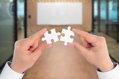 两举行连接的片断七巧板、商务联系、成功和战略概念的手 免版税库存图片