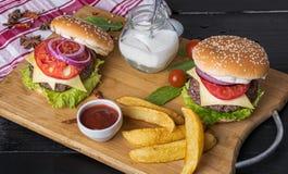 两乳酪汉堡三明治、土豆和番茄酱膳食  免版税库存图片