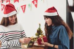 两亚洲妇女惊奇,当在节日晚会的开放金礼物盒 免版税库存照片