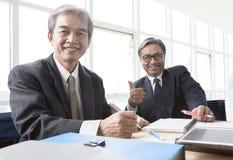 两亚洲商人暴牙的微笑的面孔,放松在offic 免版税库存照片