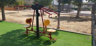 两人的训练在室外健身房的绿草的在城市公园 免版税库存图片