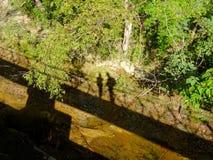 两人的阴影的图片走在一座暂停的钢桥梁的在神户,日本 免版税库存图片