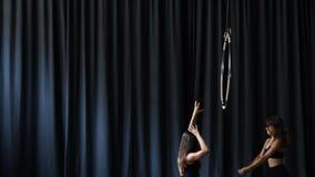 两位专业体操运动员打手势手在黑暗的帷幕背景 股票录像