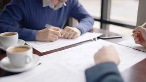 两位专家与坐在咖啡馆的桌上的图纸一起使用 股票录像