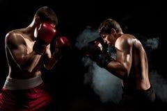 两位专家在黑发烟性背景的拳击手拳击, 图库摄影