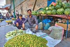 两位伊朗果子贸易商坐边路在他们的产品附近 免版税图库摄影