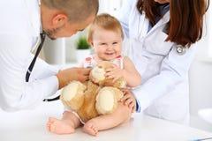 两位儿科医生在医院照顾婴孩 小女孩由有听诊器的医生审查 健康 库存图片