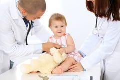 两位儿科医生在医院照顾婴孩 小女孩由有听诊器的医生审查 健康 免版税图库摄影