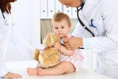 两位儿科医生在医院照顾婴孩 小女孩由有听诊器的医生审查 健康 图库摄影