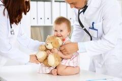 两位儿科医生在医院照顾婴孩 小女孩由有听诊器的医生审查 健康 免版税库存图片