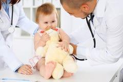 两位儿科医生在医院照顾婴孩 小女孩由有听诊器的医生审查 健康 免版税库存照片