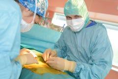 两位兽医外科医生在手术室 免版税库存照片