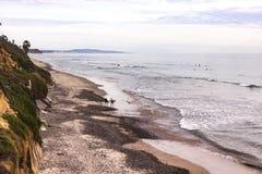 两位冲浪者走与海浪辗压和绿色山坡的一个岩石海岸线海滩 免版税库存图片