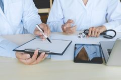 两位医生有坐在书桌的一次讨论在医院 免版税库存图片