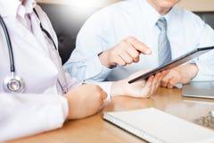 两位医生谈论耐心笔记在指向a的办公室 免版税库存图片