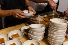 两位厨师服务点心的一种菠萝蛋糕类型在白色碗的 图库摄影