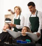 两位发式专家与客户的头发一起使用洗涤的盘子的 库存图片