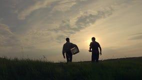 两位商人农夫坚定地与彼此握手 他们在领域谈话反对美好的日落,他们使用 股票录像