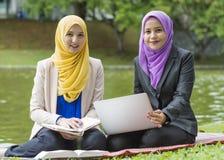 两位大学生有讨论和改变想法,当坐在公园时 免版税库存图片