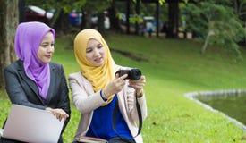 两位大学生有讨论和改变想法,当坐在公园时 免版税图库摄影