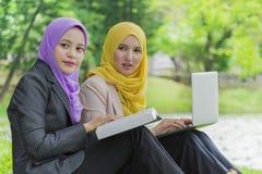两位大学生有讨论和改变想法,当坐在公园时 图库摄影