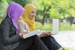 两位大学生有讨论和改变想法,当坐在公园时 库存图片