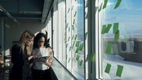 两位女性办公室在计算机窗口里校对和录音 股票录像