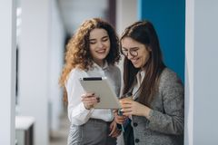 两位女性总经理谈论项目想法在数字片剂的,当走下来在办公室大厅,确信的妇女时 库存照片