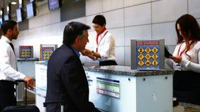两位女性检查护照和互动与通勤者的机场职员在报道登记柜台 股票视频