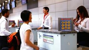 两位女性检查护照和互动与通勤者的机场职员在报道登记柜台 股票录像