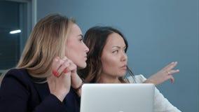 两位女性总经理谈论项目想法,当坐会议在办公室大厅时 免版税库存照片