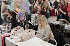 两位女推销员在与衣物辅助部件的市场上在Animefest 库存图片