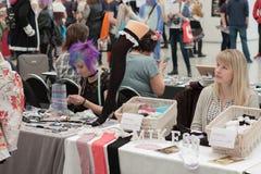 两位女推销员在与衣物辅助部件的市场上在Animefest 免版税库存照片