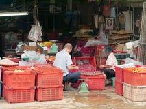 两位客商卖果子和葱在街市上 免版税库存图片