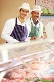 两位屠户在工作在商店 免版税库存照片