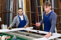 两位工作员与窗口外形一起使用 库存图片