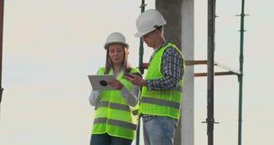 两位工程师一个男人和一名妇女有一台片剂计算机的在工地工作谴责建筑计划  股票视频