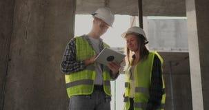 两位工程师一个男人和一名妇女有一台片剂计算机的在工地工作谴责建筑计划  股票录像