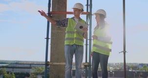 两位工程师一个男人和一名妇女有一台片剂计算机的在工地工作谴责建筑计划  影视素材