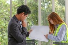 两位工程师谈论工作在候选会议地点在办公室 eng. 库存照片