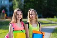 两位年轻女小学生 夏天本质上 愉快微笑 我准备好的` m去学校 拿着笔记本和文件夹的手 免版税库存照片