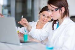 两位年轻女性研究员在实验室 图库摄影