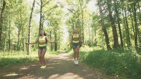 两位年轻女性跳绳在慢动作的公园 概念健康生活方式 股票录像