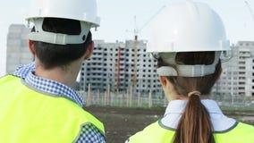 两位年轻工程师一个男人和一名妇女绿色背心和盔甲的 股票视频