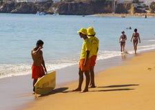 两位年轻救生员在海滩聊天给冲浪者在水渐近在Albfueria在葡萄牙 库存图片