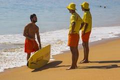 两位年轻救生员在海滩聊天给冲浪者在水渐近在Albfueria在葡萄牙 免版税库存图片