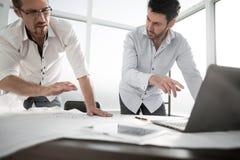 两位建筑师为工作使用一台膝上型计算机 免版税库存照片