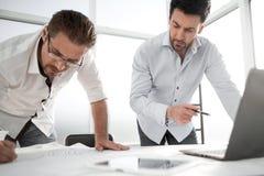 两位建筑师为工作使用一台膝上型计算机 库存图片